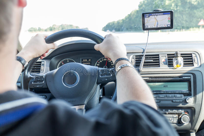 Chaufför som kör bilen med navigeringsystemet royaltyfri bild