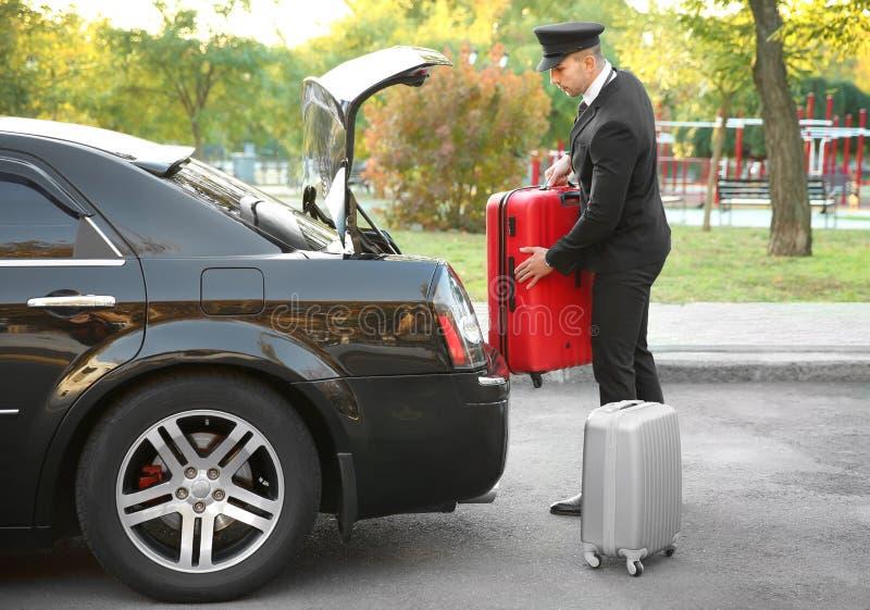 Chaufför som sätter resväskan arkivfoton
