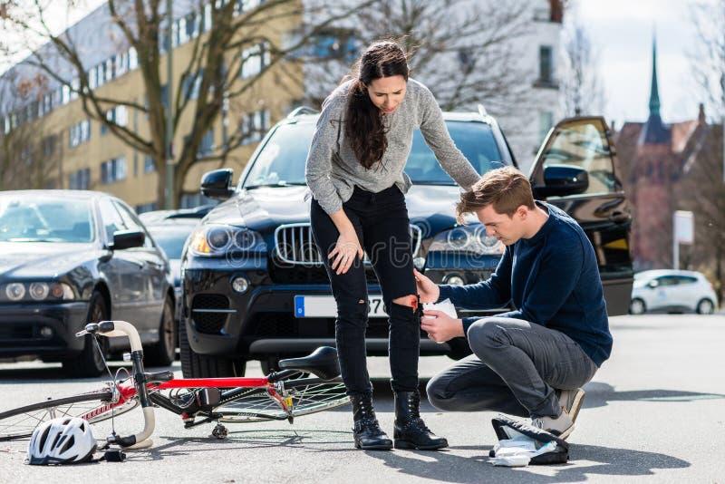 Chauffören som använder ett sterilt, förbinder för att hjälpa en sårad cyklist royaltyfri bild