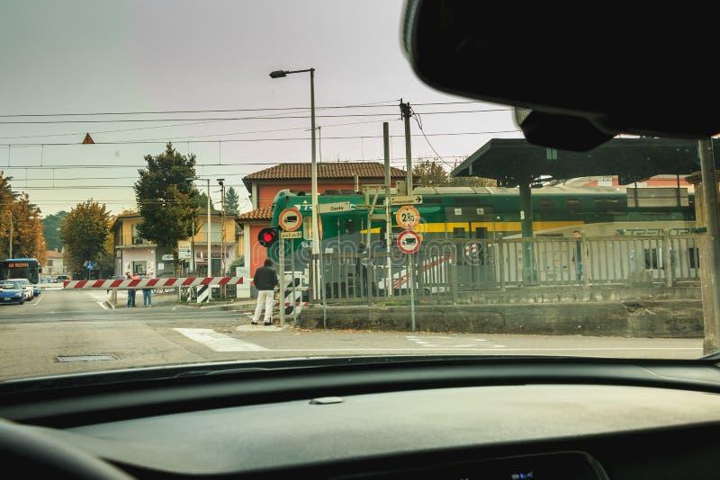 Chauffören väntar på ett drev för att passera bak portarna royaltyfria foton