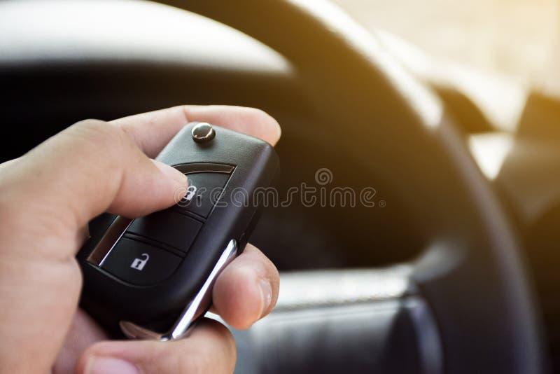 Chaufförens hand trycks på till den keyless avlägsna bilen arkivbild
