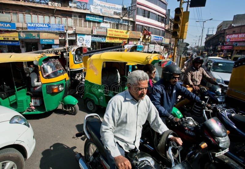 Chaufförer, bilar och rickshaws på den upptagna gatan arkivfoto