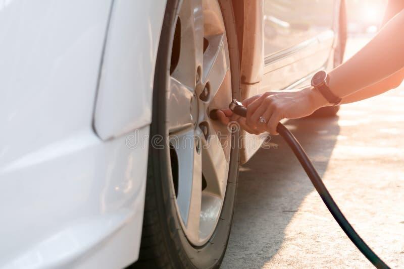 Chaufförfyllningluft in i ett bilgummihjul, gummihjulinflation arkivfoton