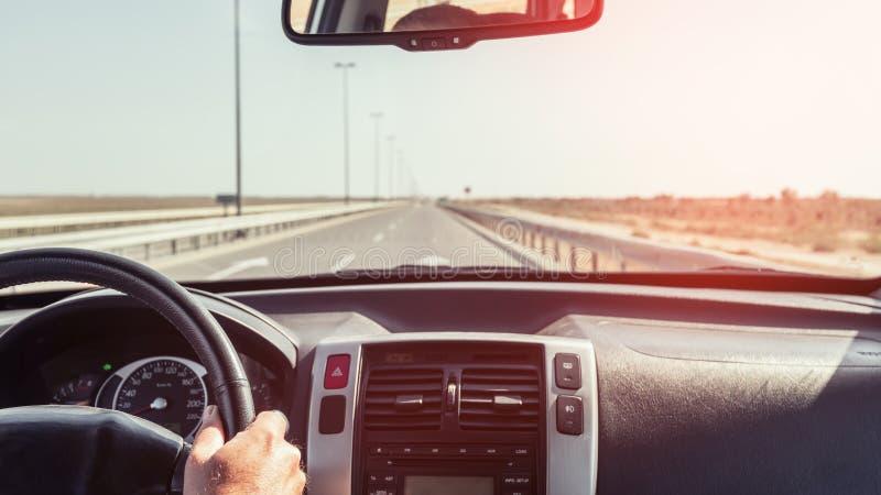 Chaufförhand på styrhjulet av en bil arkivfoto