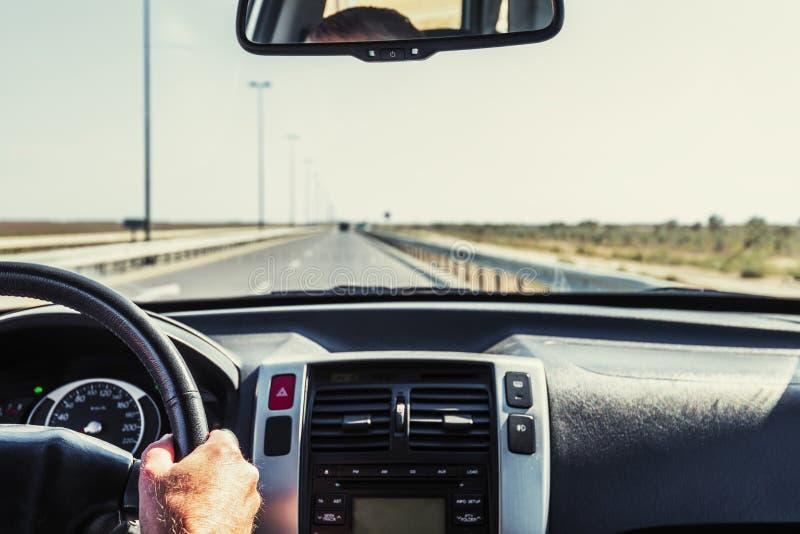 Chaufförhand på styrhjulet av en bil arkivbilder
