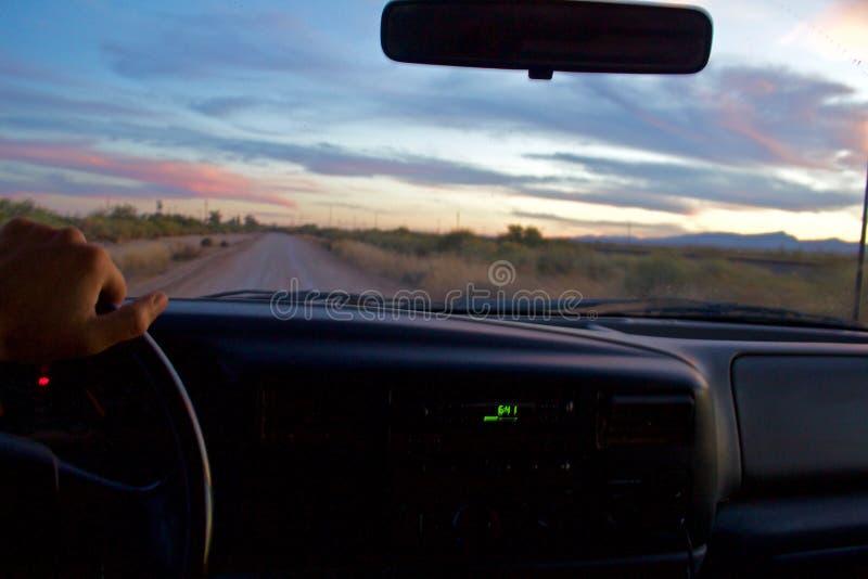 Chaufförpunkt av sikten av ett drev på en grusväg efter solnedgången, en hand på hjulet arkivfoto