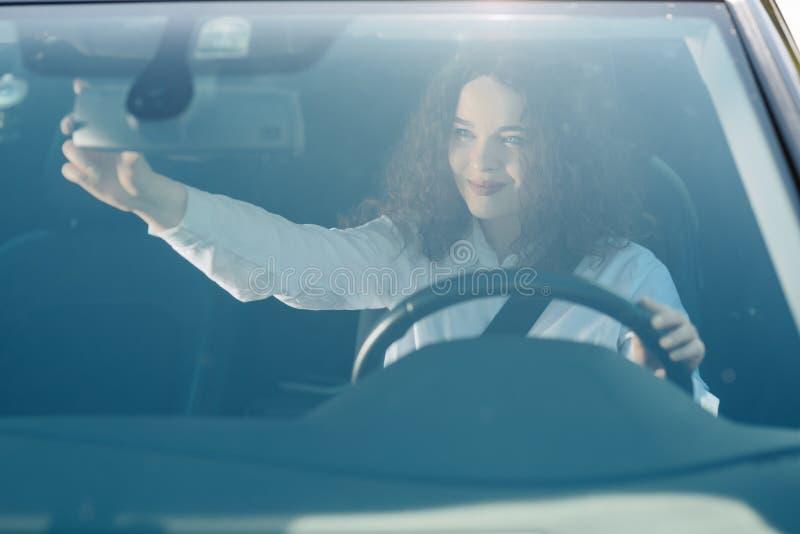 Chauff?r i backspegel Attraktiv ung kvinna i aff?rskl?der som ser i backspegel och ler, medan k?ra en bil arkivbilder