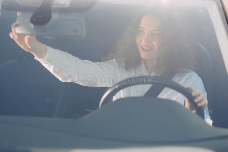 Chauff?r i backspegel Attraktiv ung kvinna i aff?rskl?der som ser i backspegel och ler, medan k?ra en bil royaltyfria foton