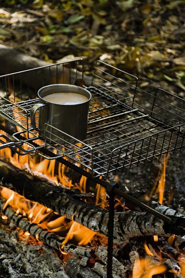 Chauffage d'une tasse de caf? tout en br?lant un feu dans un terrain de camping sauvage photos stock