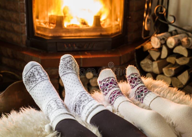 Chauffage et détente près de la cheminée Pieds de femme et d'enfant dedans pour image stock