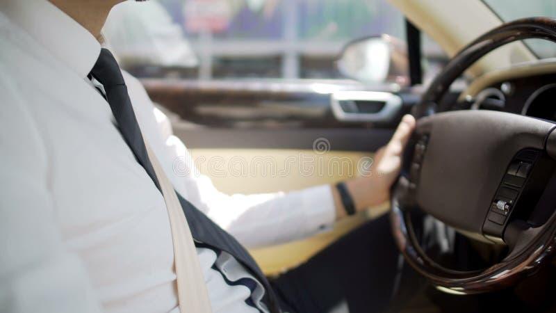 Chauffer pessoal no terno de negócio que conduz o carro luxuoso, serviços caros imagem de stock
