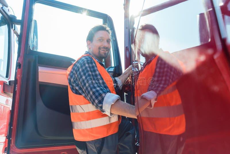 Chauffeur de camion devant son camion long-courrier image stock