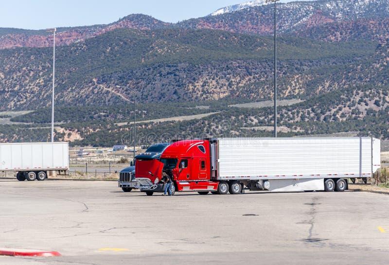 Chauffeur de camion r?parant le grand camion rouge cass? d'installation semi sur le relais routier parmi de hautes montagnes en U photo libre de droits