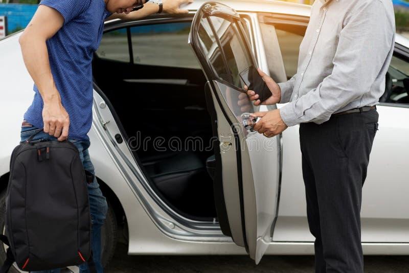 Chauffeur de taxi saluant ses passagers avec leur bagage sur le SI photos stock