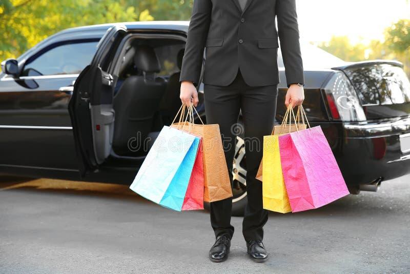 Chauffeur die kleurrijke pakken houden en zich dichtbij luxe bevinden stock foto