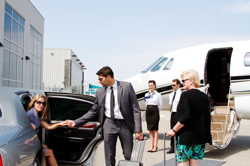 Chauffeur helping lady out of limo. Lady stepping out of limo with help of chauffeur stock photography