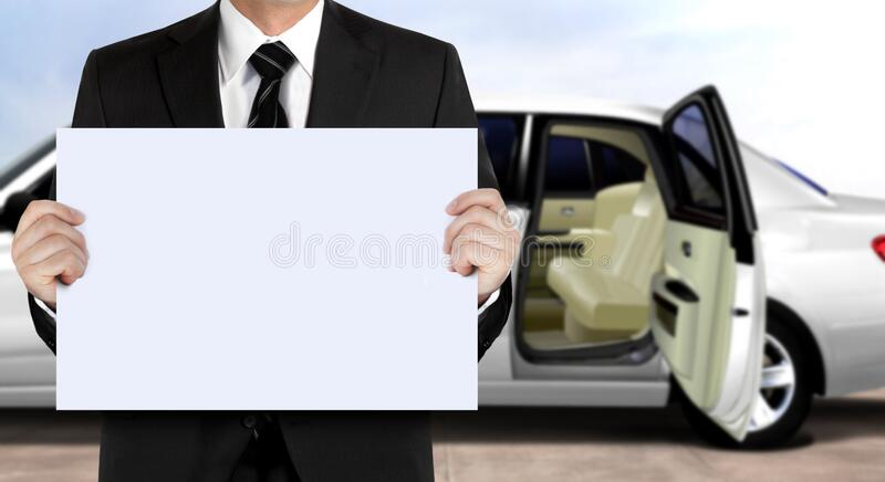 Chauffeur holding signage waiting for passenger with white limo background royalty free stock images