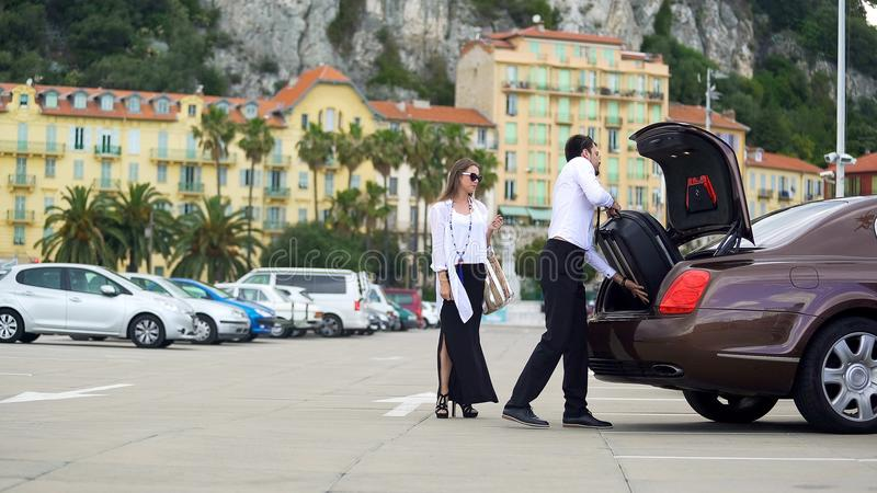 Chauffeur putting luggage in trunk, elite car service for business people stock photos