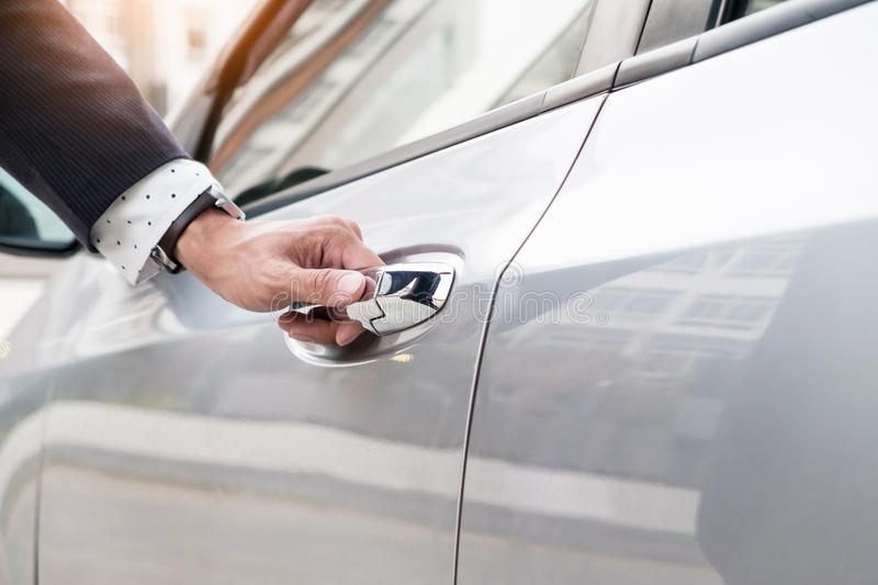 Chauffeur s hand on handle. Close-up of man in formal wear opening a passenger car door stock image