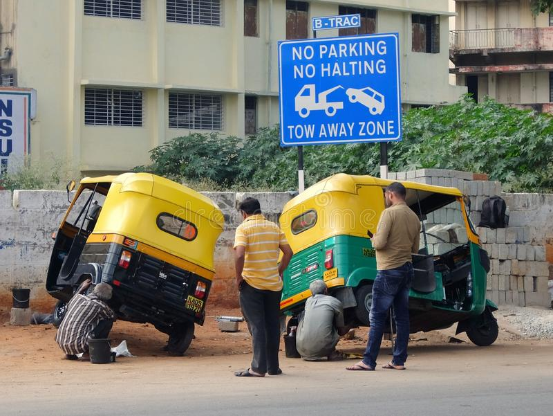 Chauffeurs de taxi sur la rue de Bangalore, réparant la voiture d'automatique-pousse-pousse, tuk-tuk image libre de droits