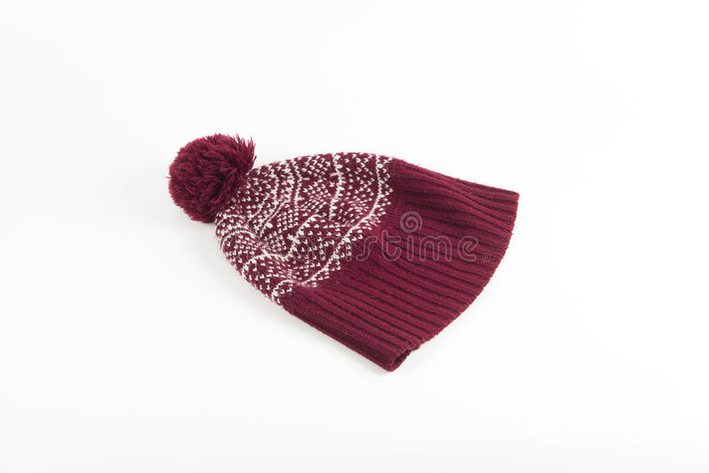 Chauffez le chapeau rouge d'hiver avec le modèle d'hiver et le pompon sur le dos de blanc image stock