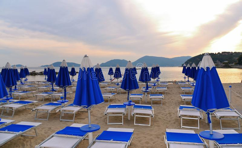 Chauffez le coucher du soleil coloré sur la plage vide avec les chaises longues bleues et l'eau de mer calme avec le vieux châtea photo stock