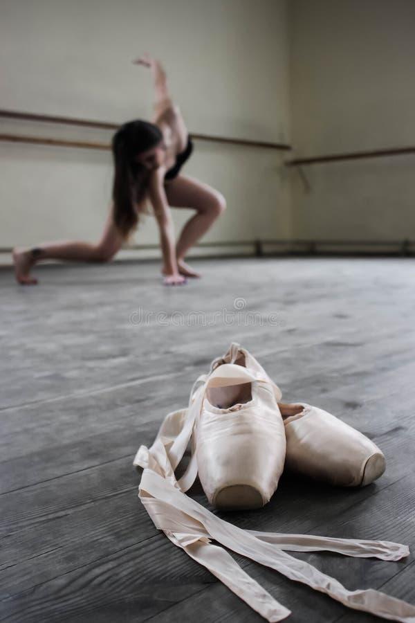 Chausse la ballerine, pointes crèmes sur le plancher foncé, fond de ballerine photo libre de droits