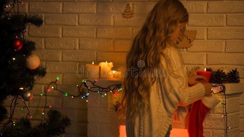 Chaussette accrochante de fille blonde aux cheveux longs sur la cheminée attendant le miracle de Santa Christmas photos stock