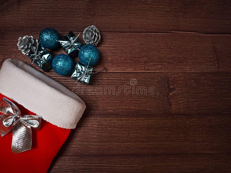 Chaussette et argent rouges, décoration bleue de Noël sur le fond en bois images stock
