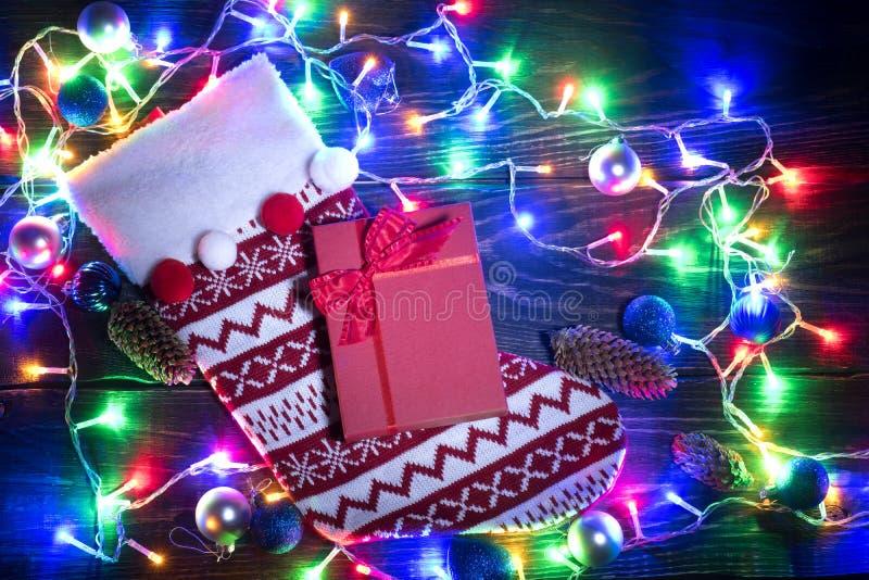Chaussette rouge de Noël et guirlande brillante photographie stock libre de droits