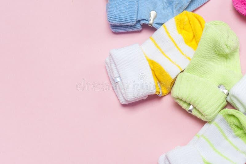 Chaussettes de bébé de coton pour nouveau-né sur un fond rose coloré Copiez l'espace photo stock
