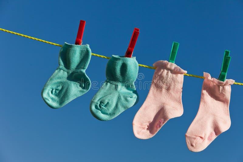 Chaussettes de chéri sur la ligne de blanchisserie à sécher photos stock