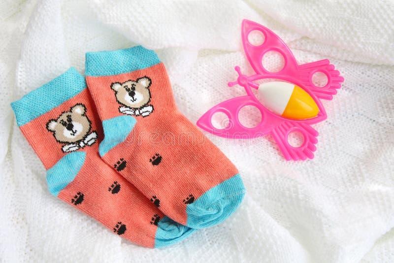 Chaussettes nouveau-nées de bébé de tricots et hochet rose coloré sur le fond blanc couvrant à crochet photos libres de droits