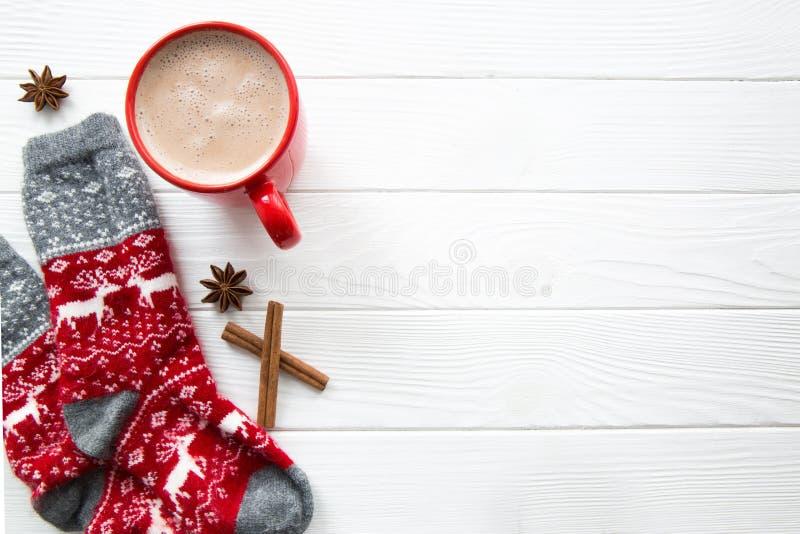 Chaussettes rouges de Noël avec les cerfs communs et l'ornement sur le backg en bois blanc photo stock