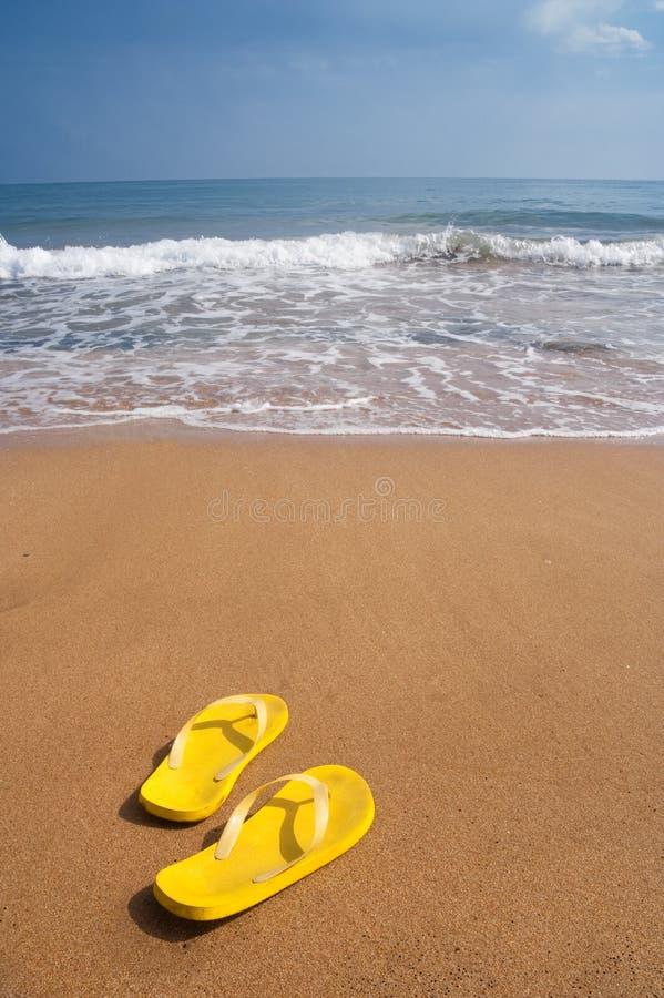 Chaussons de plage sur la plage sablonneuse images libres de droits