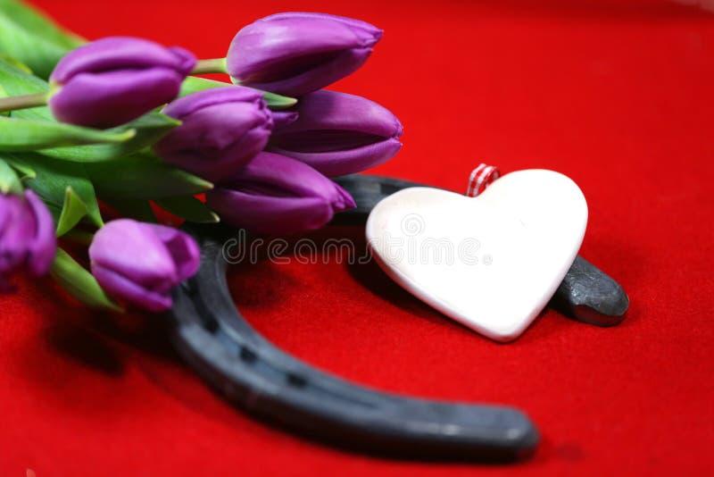Chaussure de cheval avec un coeur dans les tulipes, sur la terre rouge images stock