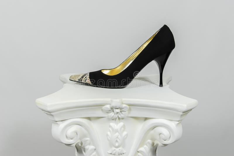 Chaussure en cuir de suède noir à talons hauts femelle élégant avec l'application de peau de serpent sur la colonne grecque images stock