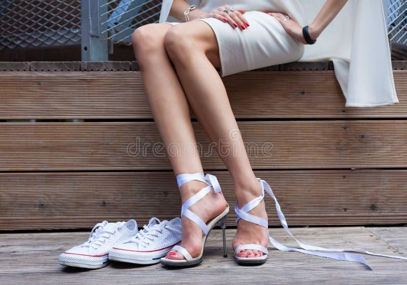 Chaussure et espadrilles de Stilleto de lien de ruban Femme à la mode avec de longues belles jambes se reposant sur un conseil en photo libre de droits