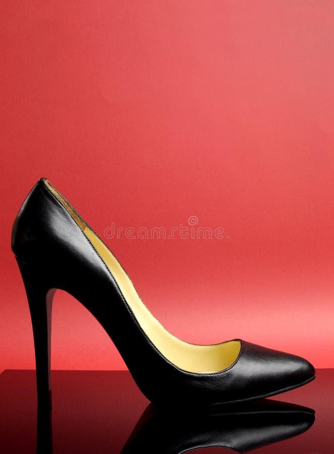 Chaussure femelle de talon haut stylet noir sur le fond rouge - verticale. image stock