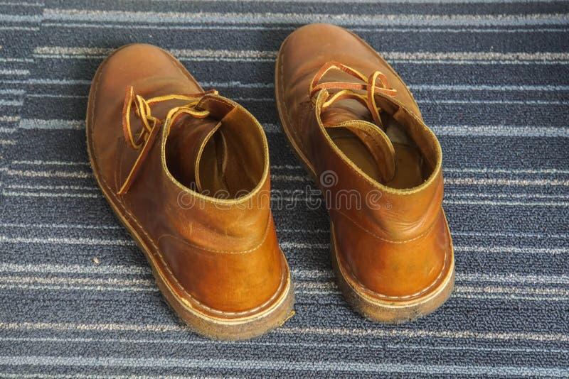 Chaussures à la mode de botte en cuir d'hommes sur le plancher images stock