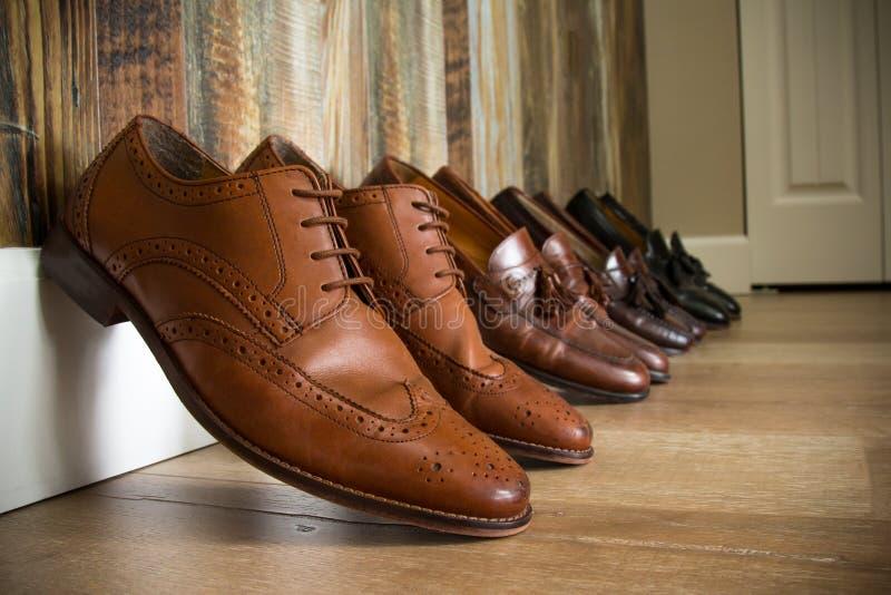 Chaussures élégantes alignées contre un mur en bois photographie stock