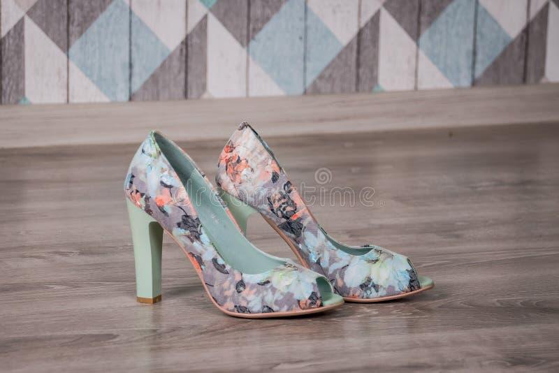 Chaussures élégantes femelles de fleurs colorées sur le plancher en bois photos libres de droits