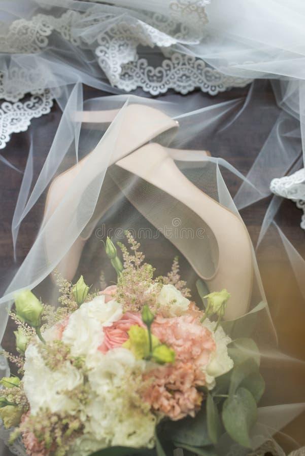 Chaussures élégantes nuptiales beiges et un bouquet couvert de voile mariage photographie stock libre de droits