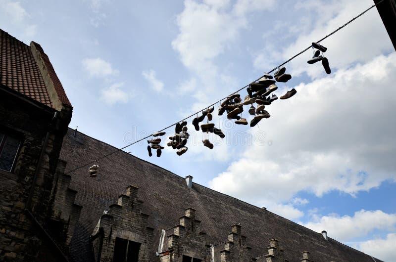 Chaussures accrochant par un fil sur une rue photos stock