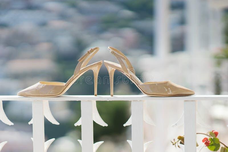 Chaussures beiges nuptiales sur une balustrade - accessoire de mariage photos stock