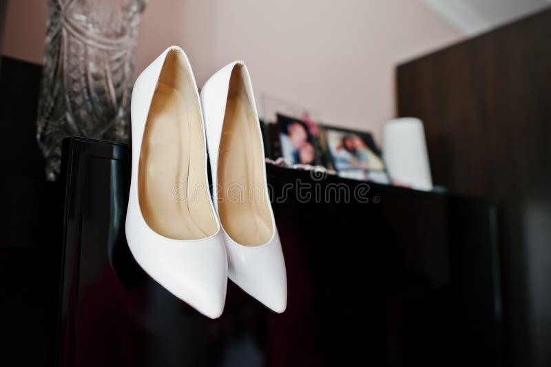 Chaussures blanches de mariage de jeune mariée sur la garde-robe noire photographie stock
