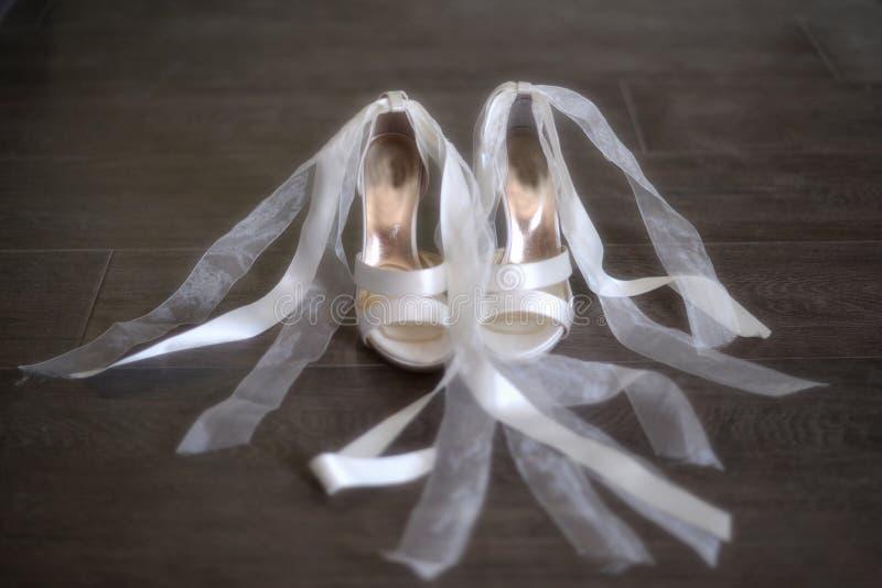 Chaussures blanches de mariage de mariées   photographie stock libre de droits