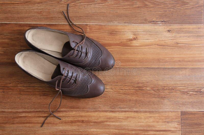Chaussures classiques marron avec lacets dénoués sur un plancher en bois photos libres de droits