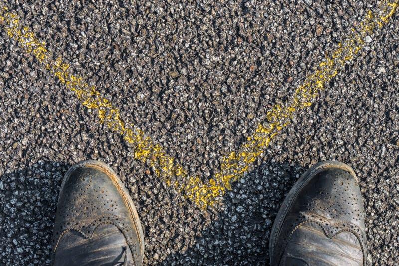 Chaussures d'affaires et marque jaune sur l'asphalte photo stock