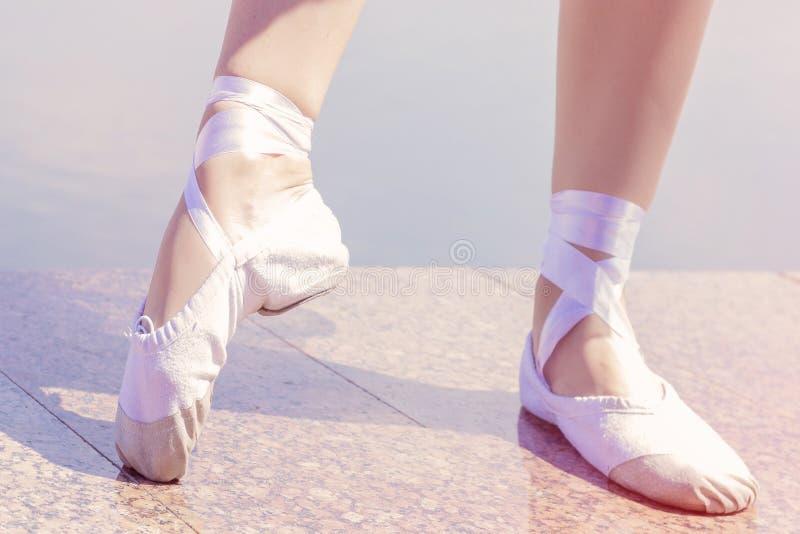 Chaussures de ballet pour danser chaussées sur leurs filles de danseur de pieds photo libre de droits